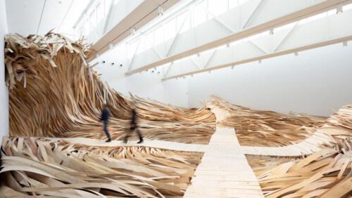 """Artikelbild für: Stürmische Rauminstallation: """"Hubris Atë Nemesis"""" – eine Welle aus Holz"""