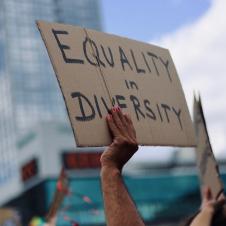"""Symbolbild für Gleichberechtigung: Arm hält Pappschild hoch, darauf steht """"Equality in Diversity"""""""
